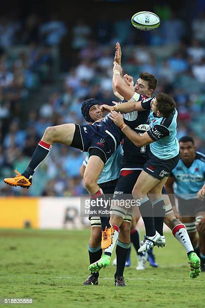 Dean Mumm of the Waratahs Jonah Placid of the Rebels and Bernard Foley of the Waratahs compete for the ball during the round six Super Rugby match...