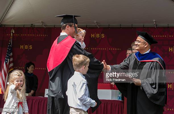 Dean Nitin Nohria of the Harvard Business School presenting his diploma to Taylor Jones with his children Jackson age 6 and Lucy age 5 months during...
