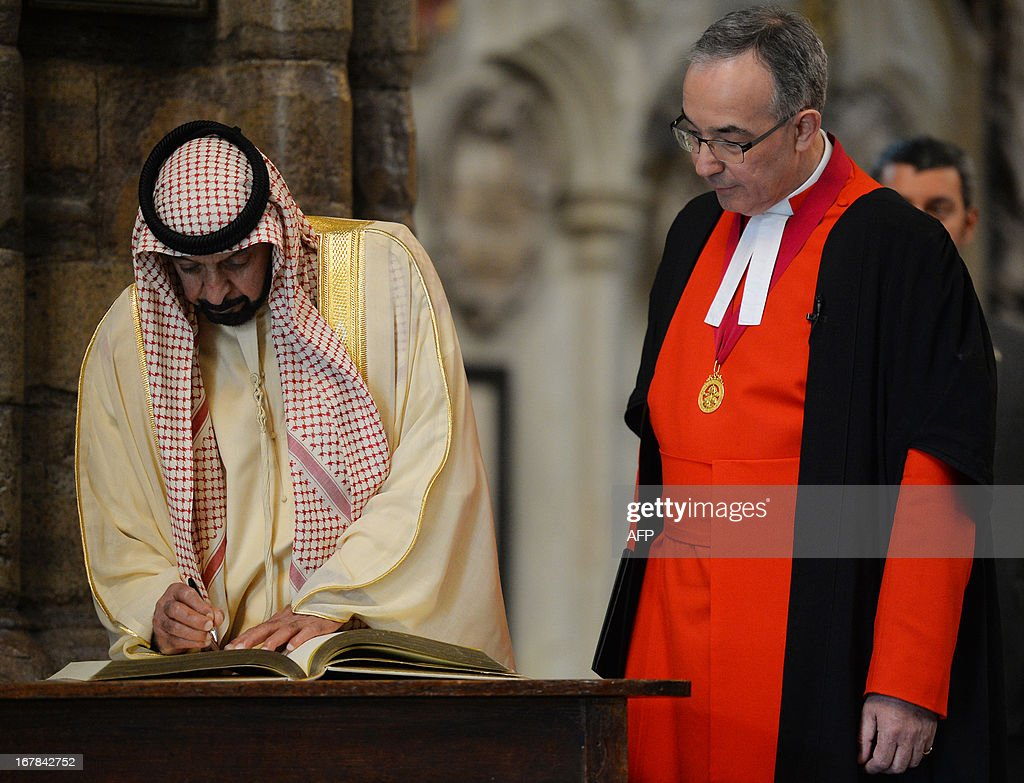 Dean of Westminster John Hall (R) looks on as Emirati President Sheikh Khalifa bin Zayed al-Nahayan (L) signs the distinguished visitors book on a tour of Westminster Abbey in central London on May 1, 2013 on the second day of his state visit to Britain. The UAE president was to face questions from Prime Minister David Cameron during a meeting over allegations that three British men jailed in Dubai were tortured.