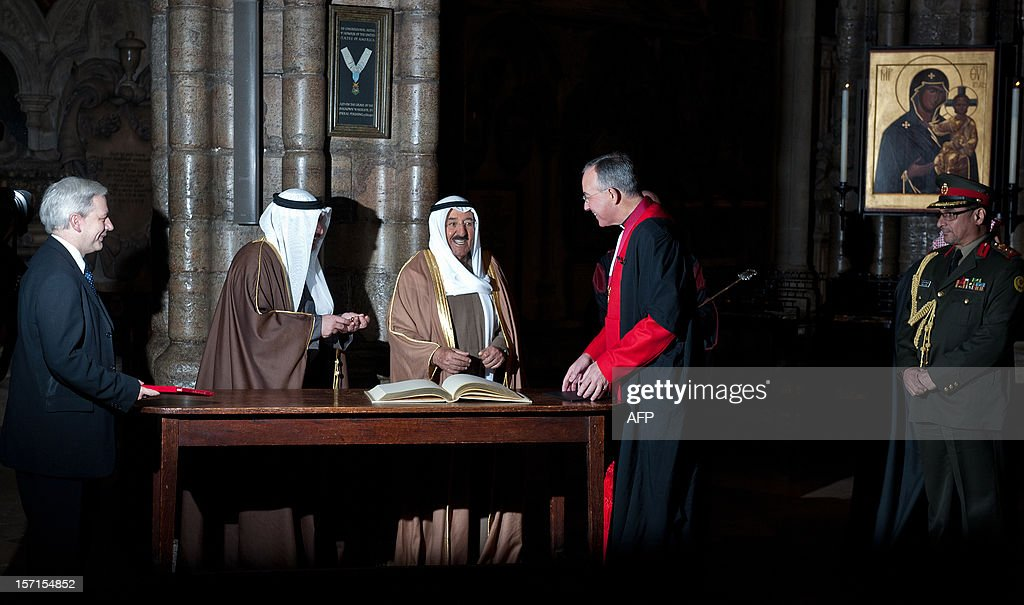 Dean of Westminster John Hall (R) looks on as the Emir of Kuwait, Sheikh Sabah al-Ahmad al-Jaber al-Sabah (C), signs the guest book during a visit to Westminster Abbey in London on November 29, 2012. The Emir of Kuwait is on day three of his state visit which is the first from Kuwait to Britain since 1995. AFP PHOTO/WILL OLIVER