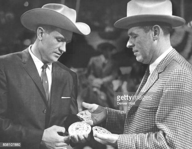 Dean Oliver left of Boise Idaho accepts trophy belt buckles from Gov John Love as symbols of his titles of World Champ Calf Roper AllAround Cowboy...