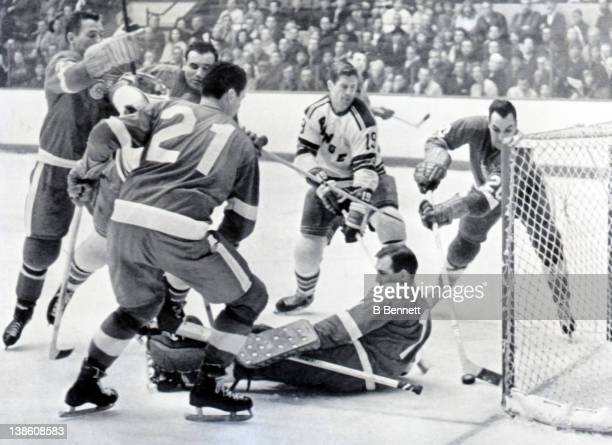 Dean Prentice of the Detroit Red Wings tries to clear the puck from behind goalie Roger Crozier as teammates Andy Bathgate Howie Young and Norm...