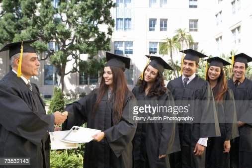 Dean presenting graduate students with awards outside college : Stock Photo