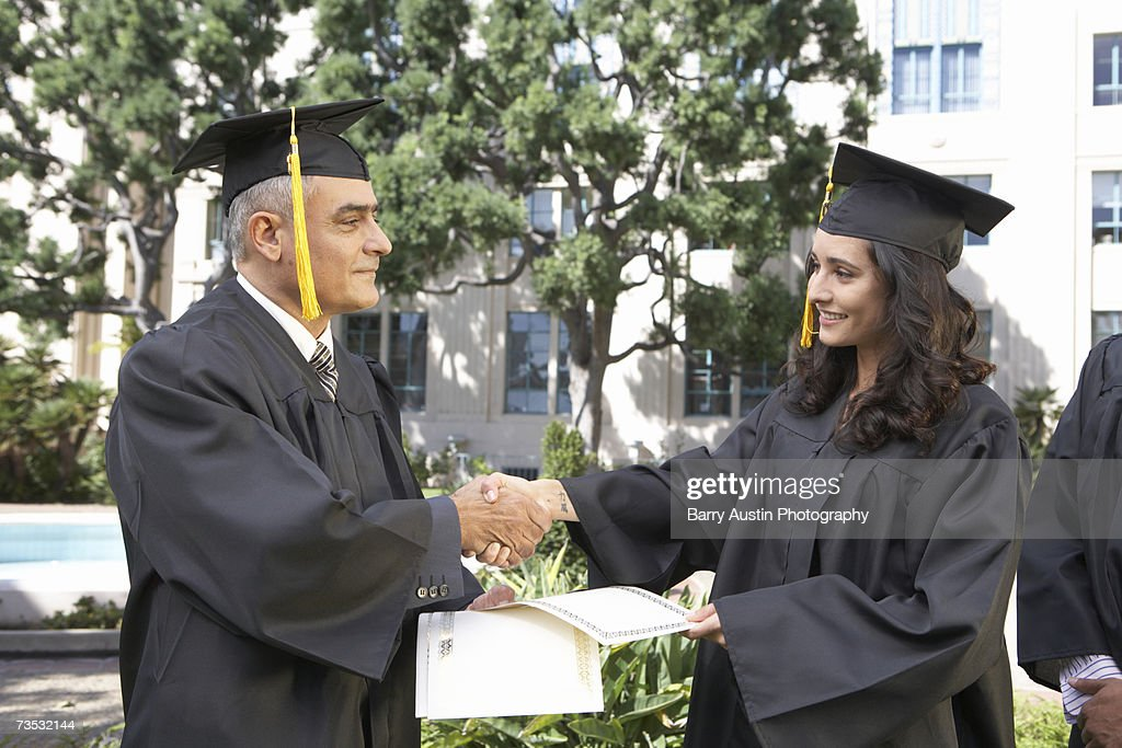 Dean presenting student with diploma at graduation ceremony : Stock Photo