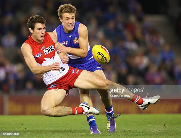 Dean Towers of the Swans handballs whilst being tackled by Jackson Macrae of the Bulldogs during the round 22 AFL match between the Western Bulldogs...