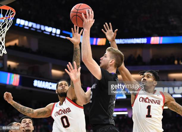 Dean Wade of the Kansas State Wildcats attempts a shot defended by Quadri Moore and Jacob Evans of the Cincinnati Bearcats during the first round of...