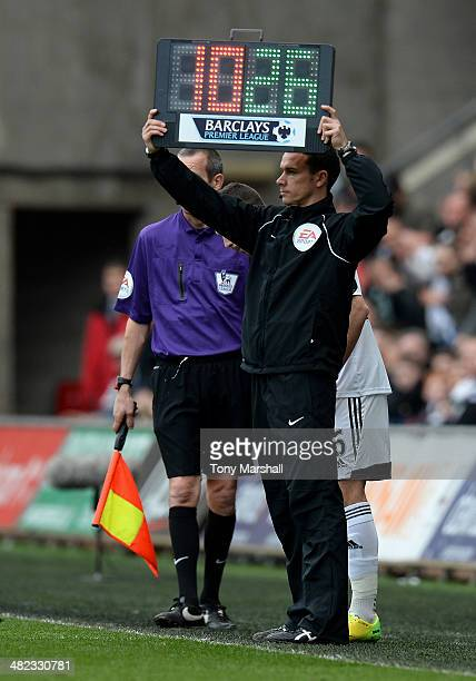 Dean Whitestone the 4th official holds up the substitution board during the Barclays Premier League match between Swansea City and Norwich City at...
