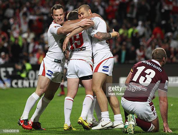 Dean Young Nathan Fien and Matt Cooper of the Dragons celebrate after Fien scored a try during the round 23 NRL match between the St George Illawarra...