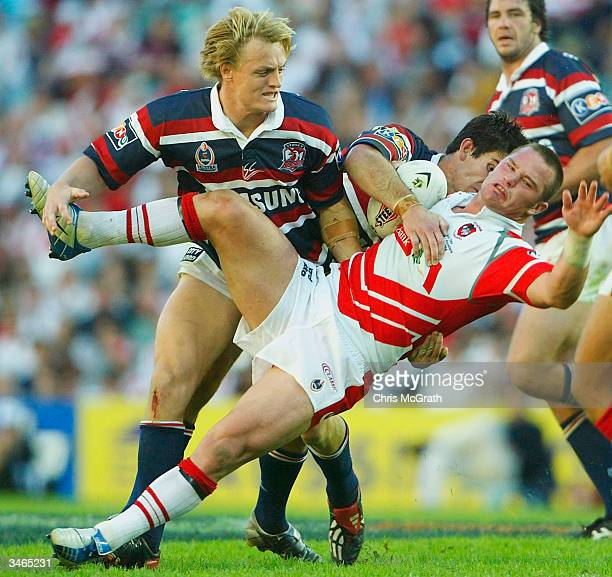 Dean Young of the Dragons is tackled by Chris Flannery and Ryan Cross of the Roosters during the NRL round seven match between the Sydney Roosters...