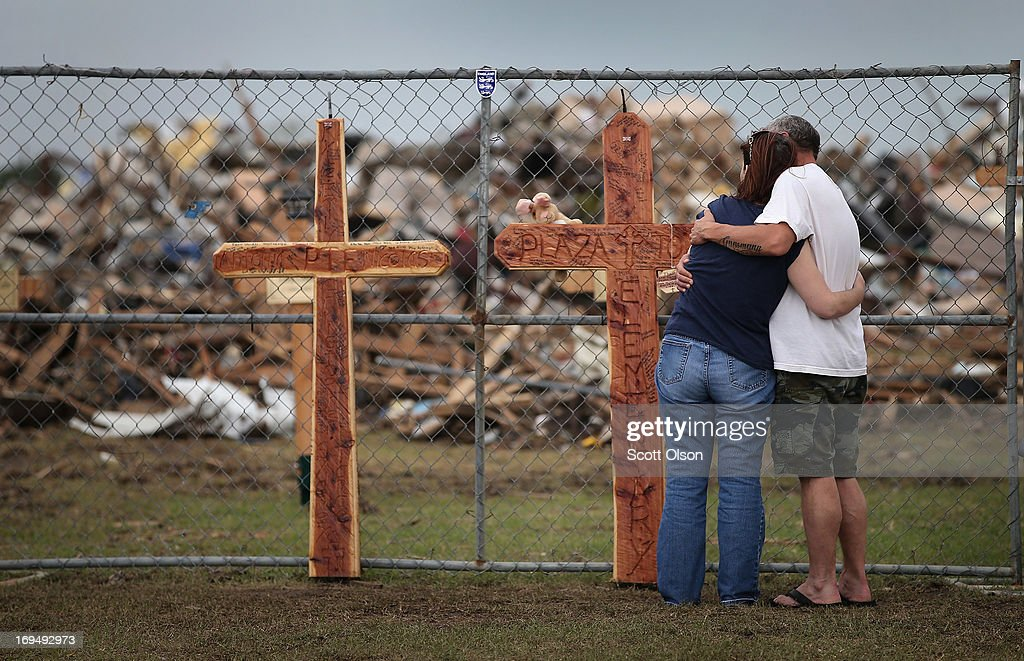 Deana Sanderson (L) and Timothy Gansman embrace as they view a memorial in front of the destroyed Plaza Towers Elementary School where seven children lost their lives during Monday's tornado on May 25, 2013 in Moore, Oklahoma. A two-mile wide EF5 tornado touched down in Moore May 20 killing at least 24 people and leaving behind extensive damage to homes and businesses. U.S. President Barack Obama promised federal aid to supplement state and local recovery efforts.