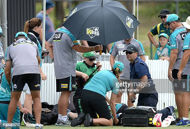 Deandra Dottin of the Heat is seen to by medical staff after colliding in the field with team mate Laura Harris during the WBBL match between the...