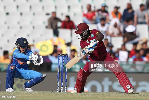 Deandra Dottin of the West Indies hits out with Sushma Verma of India looking on during the Women's ICC World Twenty20 India 2016 match between West...