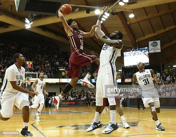 DeAndre Bembry of the Saint Joseph's Hawks attempts a dunk but Daniel Ochefu of the Villanova Wildcats fouls Bembry on the play on December 6 2014 at...