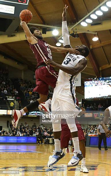 DeAndre Bembry of the Saint Joseph's Hawks attempts a dunk but Daniel Ochefu of the Villanova Wildcats fouls Bembry on the play on December 6 2014 at...