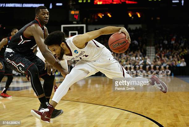 DeAndre Bembry of the Saint Joseph's Hawks drives against Coreontae DeBerry Cincinnati Bearcats in the first half during the first round of the 2016...