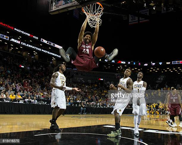 DeAndre Bembry of the Saint Joseph's Hawks dunks the ball against Mo AlieCox Melvin Johnson and JeQuan Lewis of the Virginia Commonwealth Rams in the...