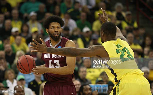 DeAndre Bembry of the Saint Joseph's Hawks looks to pass against Elgin Cook of the Oregon Ducks in the first half during the second round of the 2016...