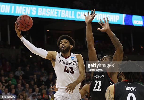 DeAndre Bembry of the Saint Joseph's Hawks shoots against Coreontae DeBerry and Quadri Moore of the Cincinnati Bearcats in the first half during the...