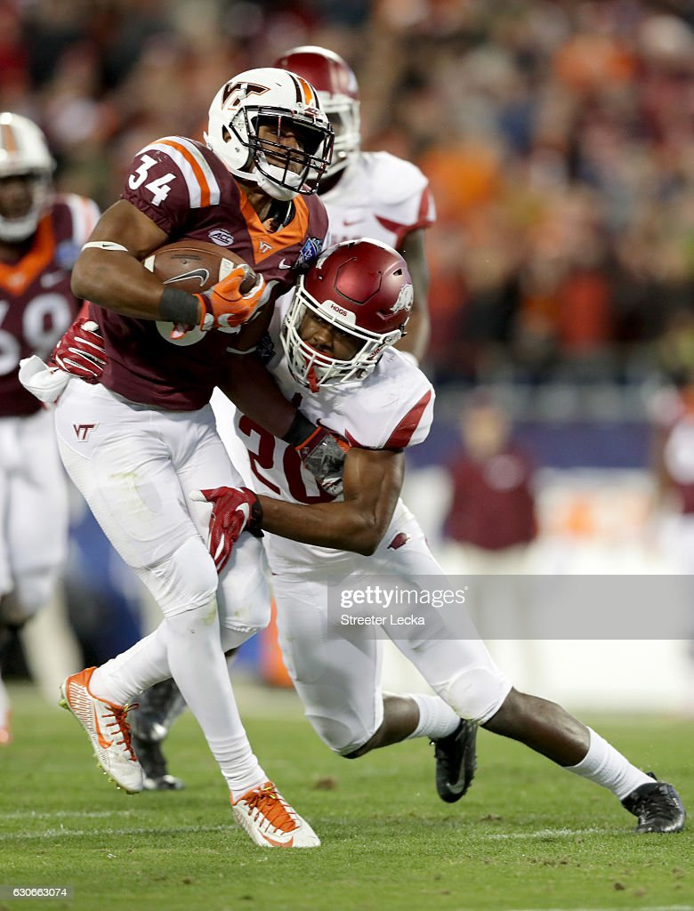 De'Andre Coley #20 of the Arkansas Razorbacks tries to stop Travon McMillian #34 of the Virginia Tech Hokies during the Belk Bowl at Bank of America Stadium on December 29, 2016 in Charlotte, North Carolina.