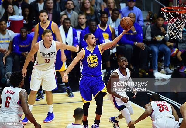 DeAndre Jordan Blake Griffin Chris Paul and Jamaal Crawford of the Los Angeles Clippers watch as Steph Curry of the Golden State Warriors scores...