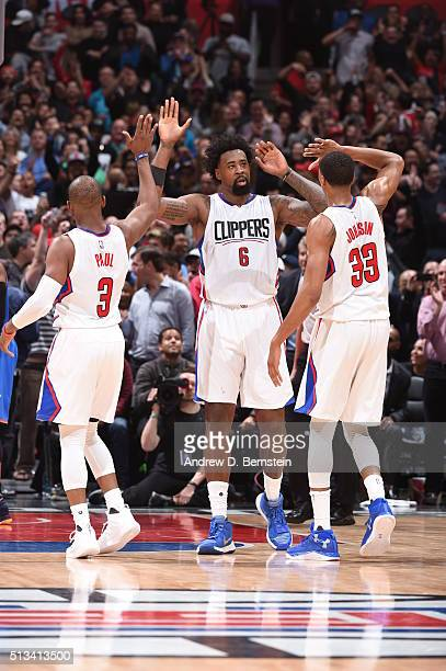 DeAndre Jordan high fives teammates Chris Paul and Wesley Johnson of the Los Angeles Clippers during the game against the Oklahoma City Thunder on...