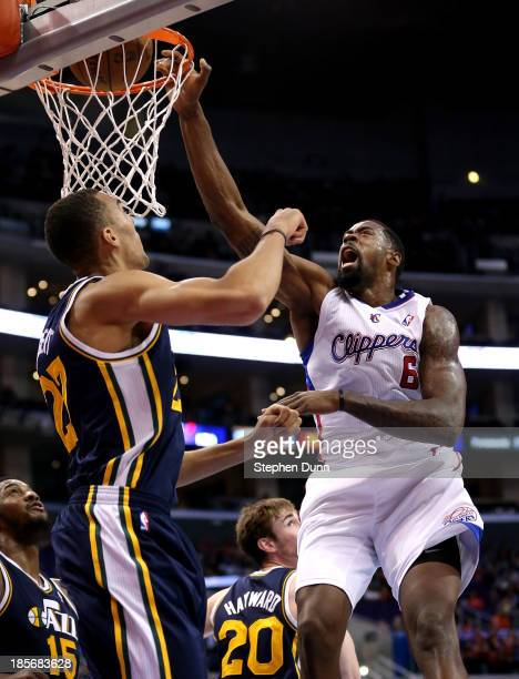 DeAndre Jordan of the Los Angeles Clippers dunks over Rudy Gobert of the Utah Jazz at Staples Center on October 23 2013 in Los Angeles California...