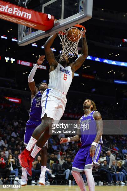 DeAndre Jordan of the Los Angeles Clippers dunks the ball against Willie CauleyStein and Buddy Hield of the Sacramento Kings on October 12 2017 at...