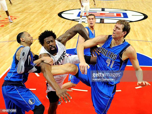 DeAndre Jordan of the Los Angeles Clippers is fouled by Dirk Nowitzki and Devin Harris of the Dallas Mavericks during the second quarter of the...