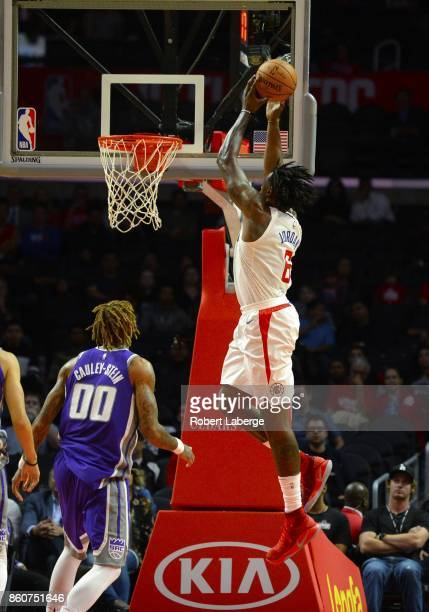 DeAndre Jordan of the Los Angeles Clippers makes a dunk against Willie CauleyStein of the Sacramento Kings on October 12 2017 at STAPLES Center in...