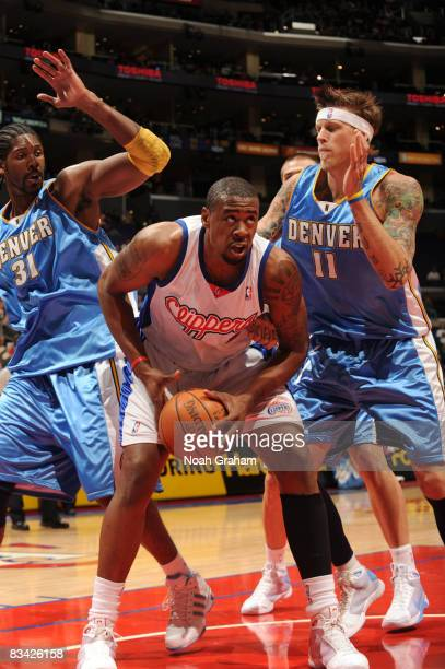 DeAndre Jordan of the Los Angeles Clippers powers his way to the basket between Nene and Chris Andersen of the Denver Nuggets at Staples Center on...