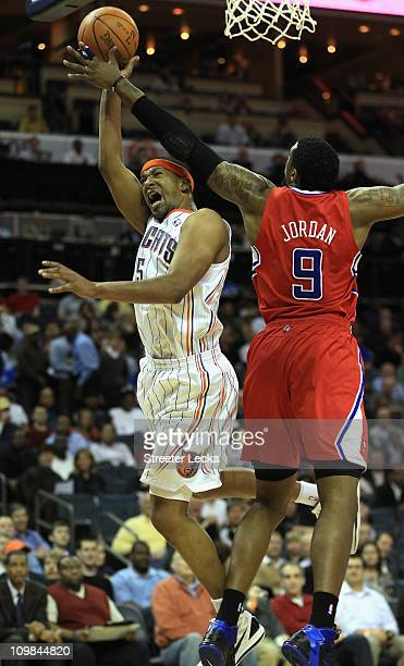 DeAndre Jordan of the Los Angeles Clippers tries to stop Dominic McGuire of the Charlotte Bobcats during their game at Time Warner Cable Arena on...