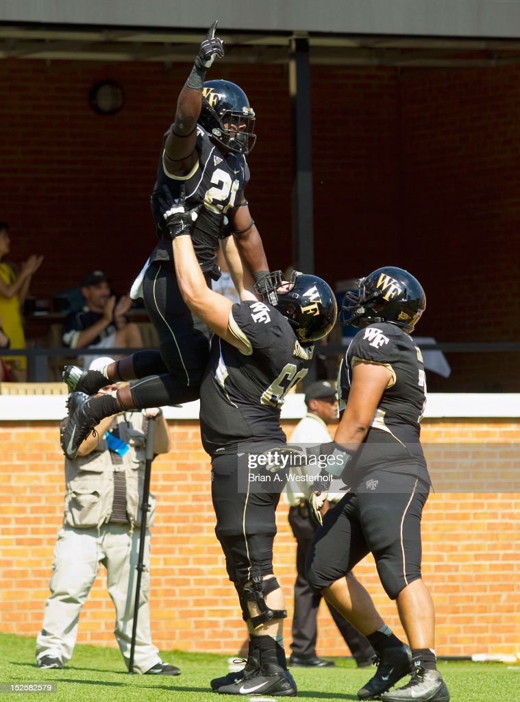 Deandre Martin of the Wake Forest Demon Deacons is lifted into the air by teammate Colin Summers after scoring a touchdown against the Army Black...