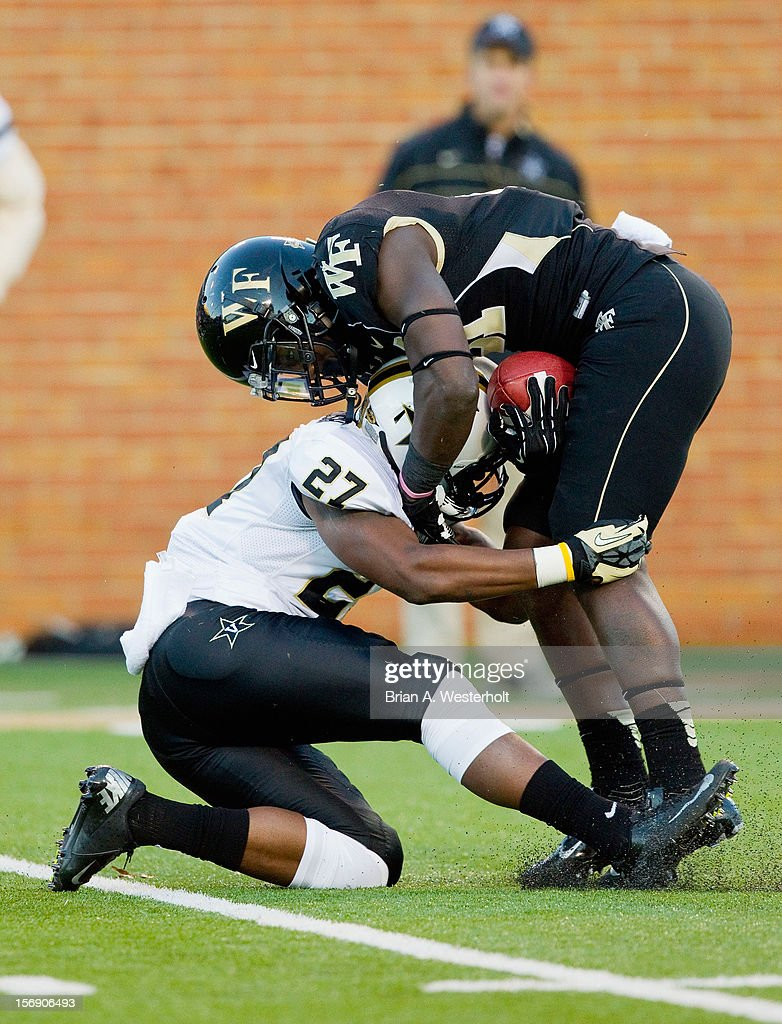 Deandre Martin #21 of the Wake Forest Demon Deacons is stopped in his tracks by Jahmel McIntosh #27 of the Vanderbilt Commodores at BB&T Field on November 24, 2012 in Winston Salem, North Carolina.