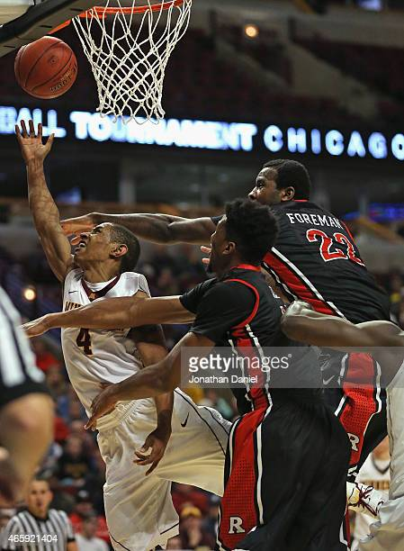 DeAndre Mathieu of the Minnesota Golden Gophers puts up a shot past Kadeem Jack and Jalen Hyde of the Rutgers Scarlet Knights during the first round...