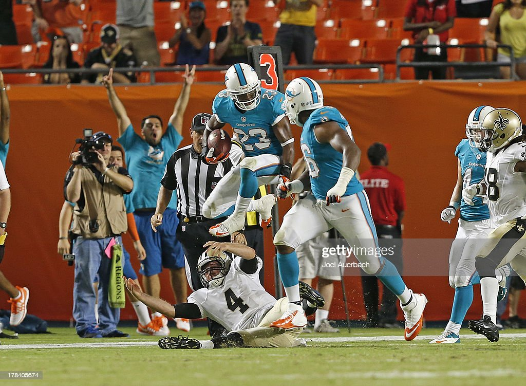 De'Andre Presley #23 of the Miami Dolphins runs with the ball over Ryan Griffin #4 of the New Orleans Saints after intercepting a pass with one minute left during a preseason game on August 29, 2013 at Sun Life Stadium in Miami Gardens, Florida. The Dolphins defeated the Saints 24-21.