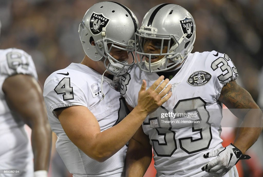 DeAndre Washington #33 of the Oakland Raiders is congratulated by Derek Carr #4 after Washington scored a touchdown against the Kansas City Chiefs during their NFL football game at Oakland-Alameda County Coliseum on October 19, 2017 in Oakland, California.