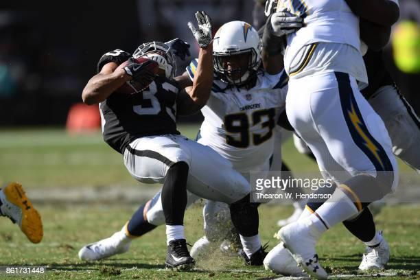 DeAndre Washington of the Oakland Raiders is tackled by his facemask by Darius Philon of the Los Angeles Chargers during their NFL game at...