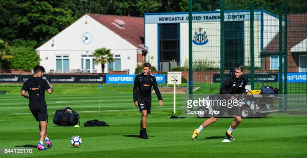 DeAndre Yedlin passes the ball to Florian Lejeune whilst Dwight Gayle looks on during the Newcastle United Training session at the Newcastle United...