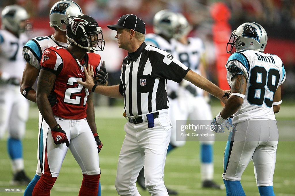 DeAngelo Hall of the Atlanta Falcons is separated from Steve Smith of the Carolina Panthers by Side Judge Carl Cheffers during the game at the...