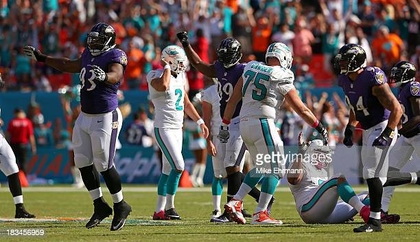 DeAngelo Tyson and Chris Canty of the Baltimore Ravens react to Brandon Fields of the Miami Dolphins missing a kick late in the fourth quarter during...
