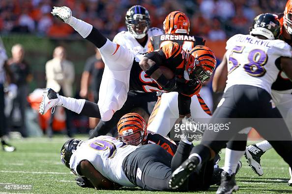 DeAngelo Tyson of the Baltimore Ravens knocks Jeremy Hill of the Cincinnati Bengals off of his feet during the second quarter at Paul Brown Stadium...