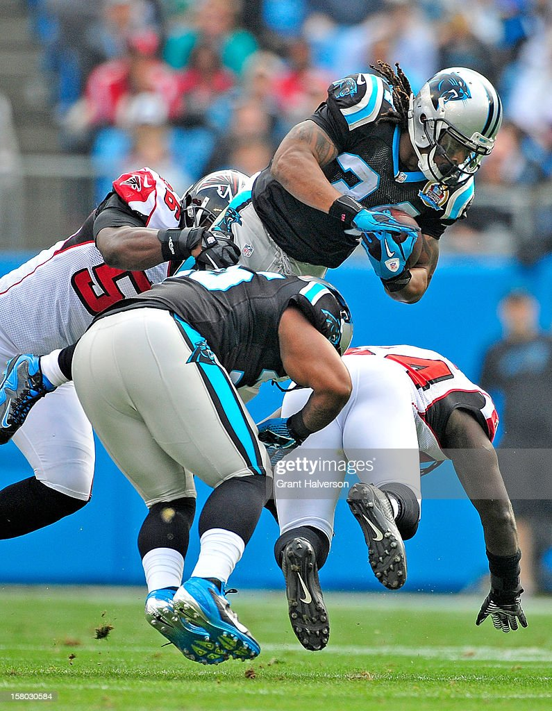 DeAngelo Williams #34 of the Carolina Panthers attempts to hurdle Sean Weatherspoon #56 and Stephen Nichols #54 of the Atlanta Falcons during play at Bank of America Stadium on December 9, 2012 in Charlotte, North Carolina.