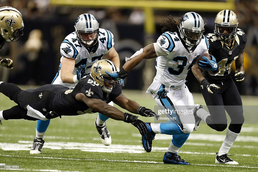DeAngelo Williams #34 of the Carolina Panthers avoids the tackle of Curtis Lofton #50 of the New Orleans Saints at Mercedes-Benz Superdome on December 30, 2012 in New Orleans, Louisiana. The Panthers defeated the Saints 44-38.