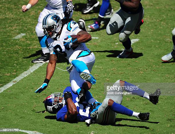 DeAngelo Williams of the Carolina Panthers carries the ball against Ryan Mundy of the New York Giants at Bank of America Stadium on September 22 2013...