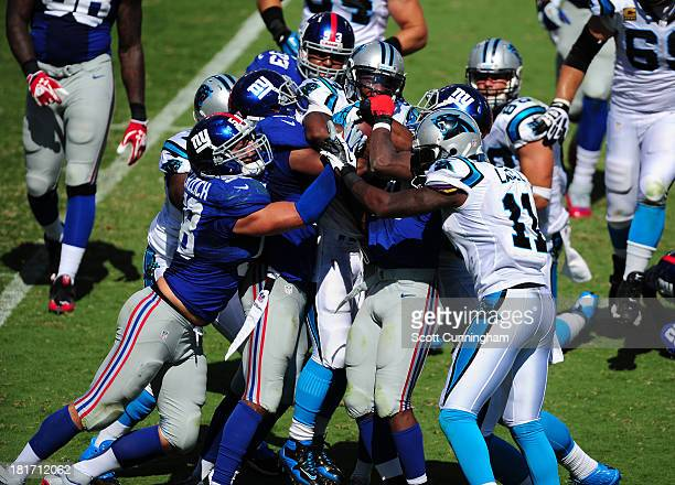 DeAngelo Williams of the Carolina Panthers is stood up bt Ryan Mundy Prince Amukamara and Mark Herzlich of the New York Giants at Bank of America...