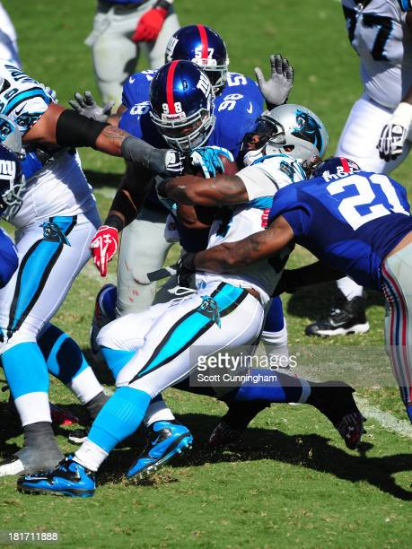DeAngelo Williams of the Carolina Panthers is tackled by Ryan Mundy and Damontre Moore of the New York Giants at Bank of America Stadium on September...