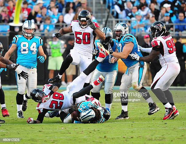 DeAngelo Williams of the Carolina Panthers is tackled by Thomas DeCoud and Peria Jerry of the Atlanta Falcons at Bank of America Stadium on November...