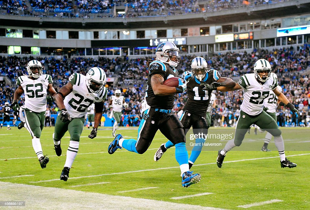 DeAngelo Williams #34 of the Carolina Panthers outruns Ed Reed #22 and the New York Jets defense for a touchdown during the second quarter at Bank of America Stadium on December 15, 2013 in Charlotte, North Carolina.