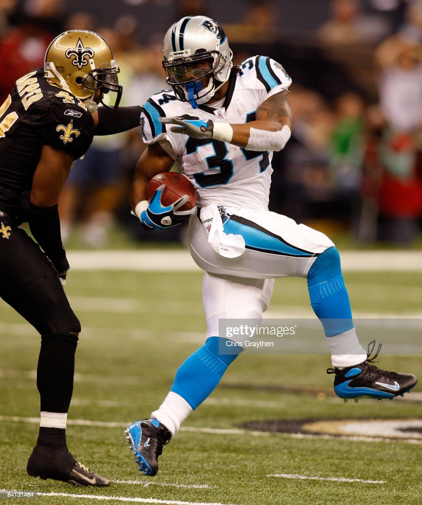 DeAngelo Williams of the Carolina Panthers tries to avoid a tackle by Roman Harper of the New Orleans Saints on December 28 2008 at the Superdome in...