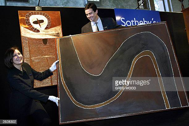 Deanna Cook and Nick Resch from Sotheby's display a painting by Aboriginal artist Rover Thomas with another by Alec Mingelmanganu in Sydney 29 July...